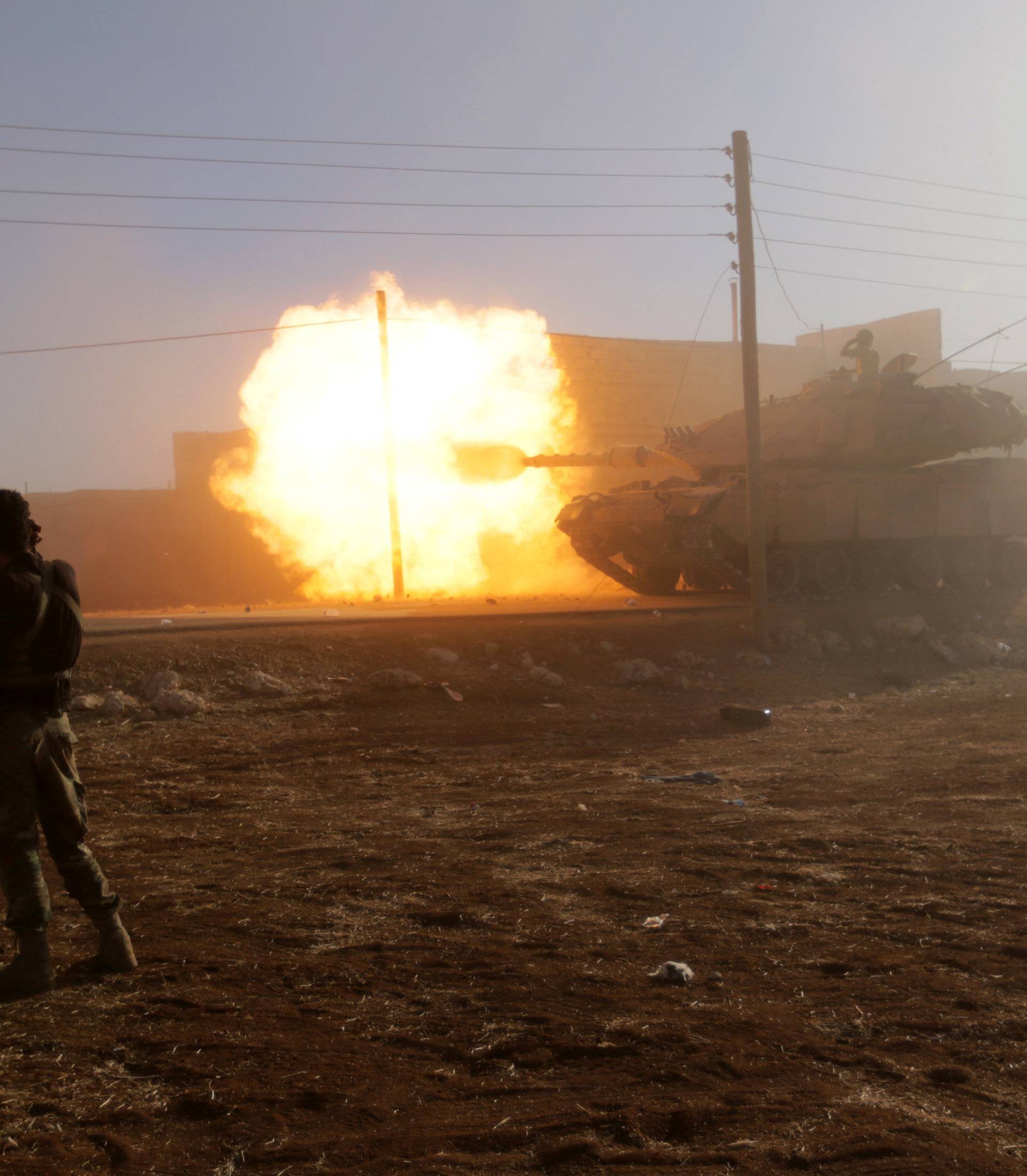 A rebel fighter stands near a Turkish tank as it fires towards Guzhe village, northern Aleppo countryside