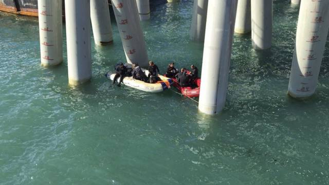 Rescuers work near a pier after a bus carrying a group of workers plunged into the Black Sea in the Krasnodar region