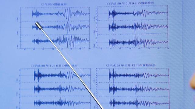 Japan Meteorological Agency's earthquake and tsunami observations division director Matsumori points at graphs of ground motion waveform data observed in Japan during a news conference at the Japan Meteorological Agency in Tokyo