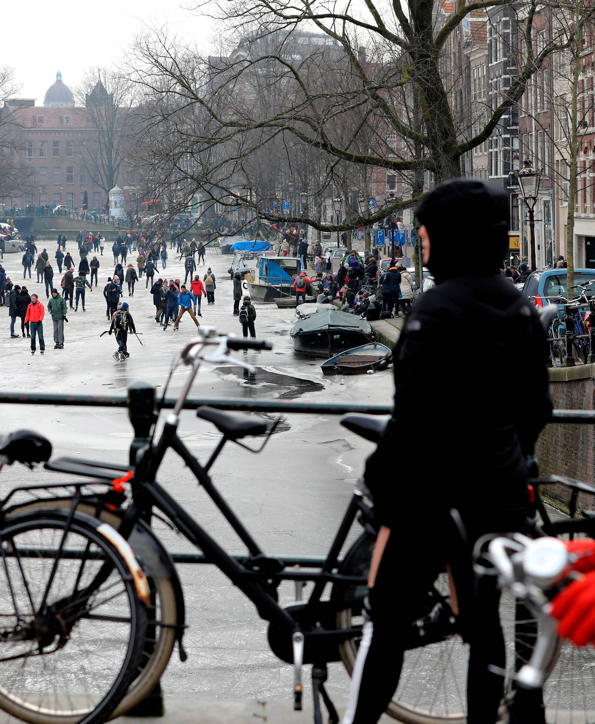 Cyclists look at ice skaters on the frozen Prinsengracht canal during icy weather in Amsterdam