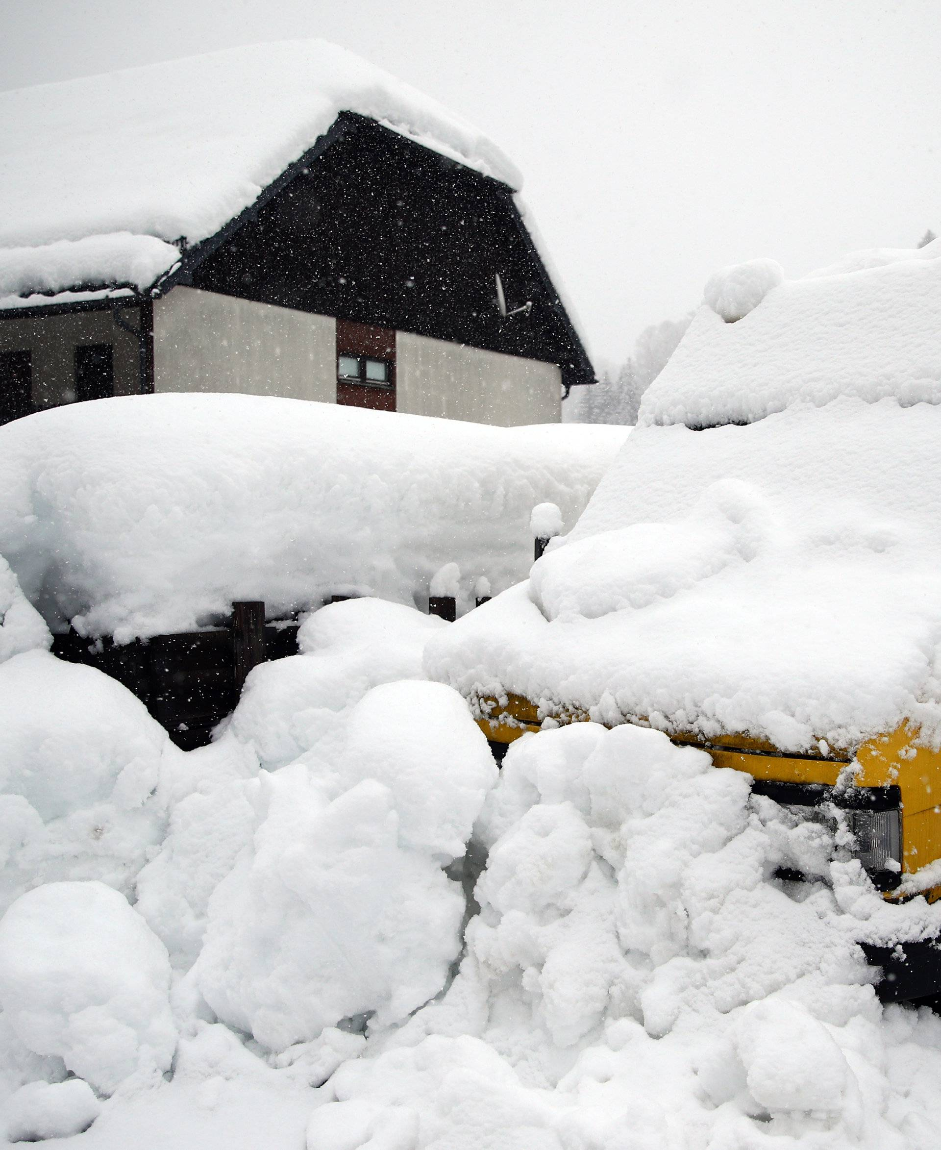 A parked car is covered with snow in Goestling