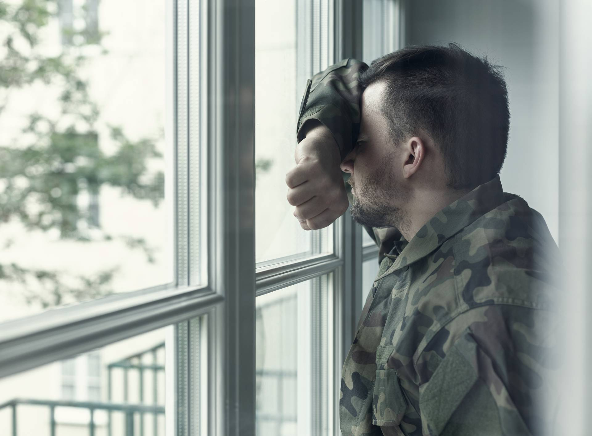Depressed and sad soldier in green uniform with trauma after war standing near the window