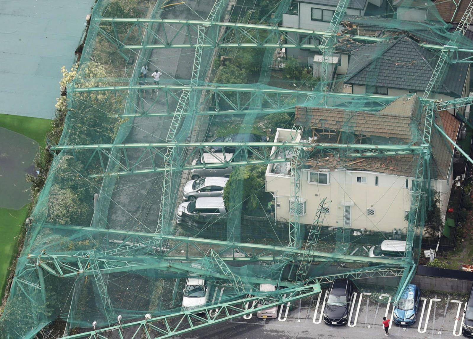 Houses and cars damaged by a collapse of the perimeter netting of a golf training field due to strong winds of Typhoon Faxai are seen in Ichihara