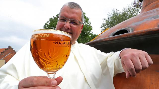 Norbertine Father Karel poses with a Grimbergen beer, symbolised by a phoenix, in the courtyard of the Belgian Abbey of Grimbergen before announcing that the monks will return to brewing after a break of two centuries, in Grimbergen