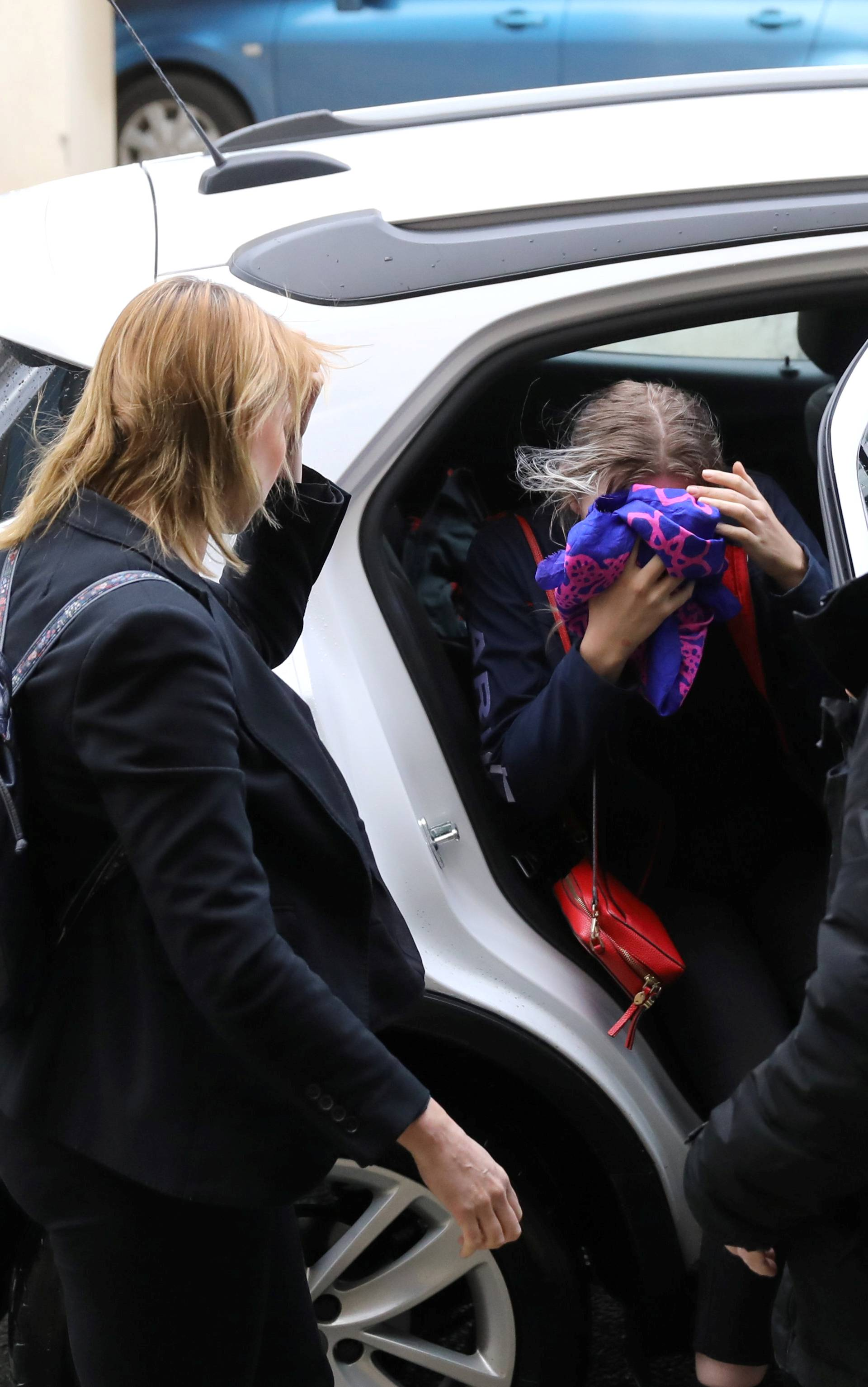 A British woman, accused of lying about being gang raped, covers her face as she arrives at the Famagusta courthouse in Paralimni
