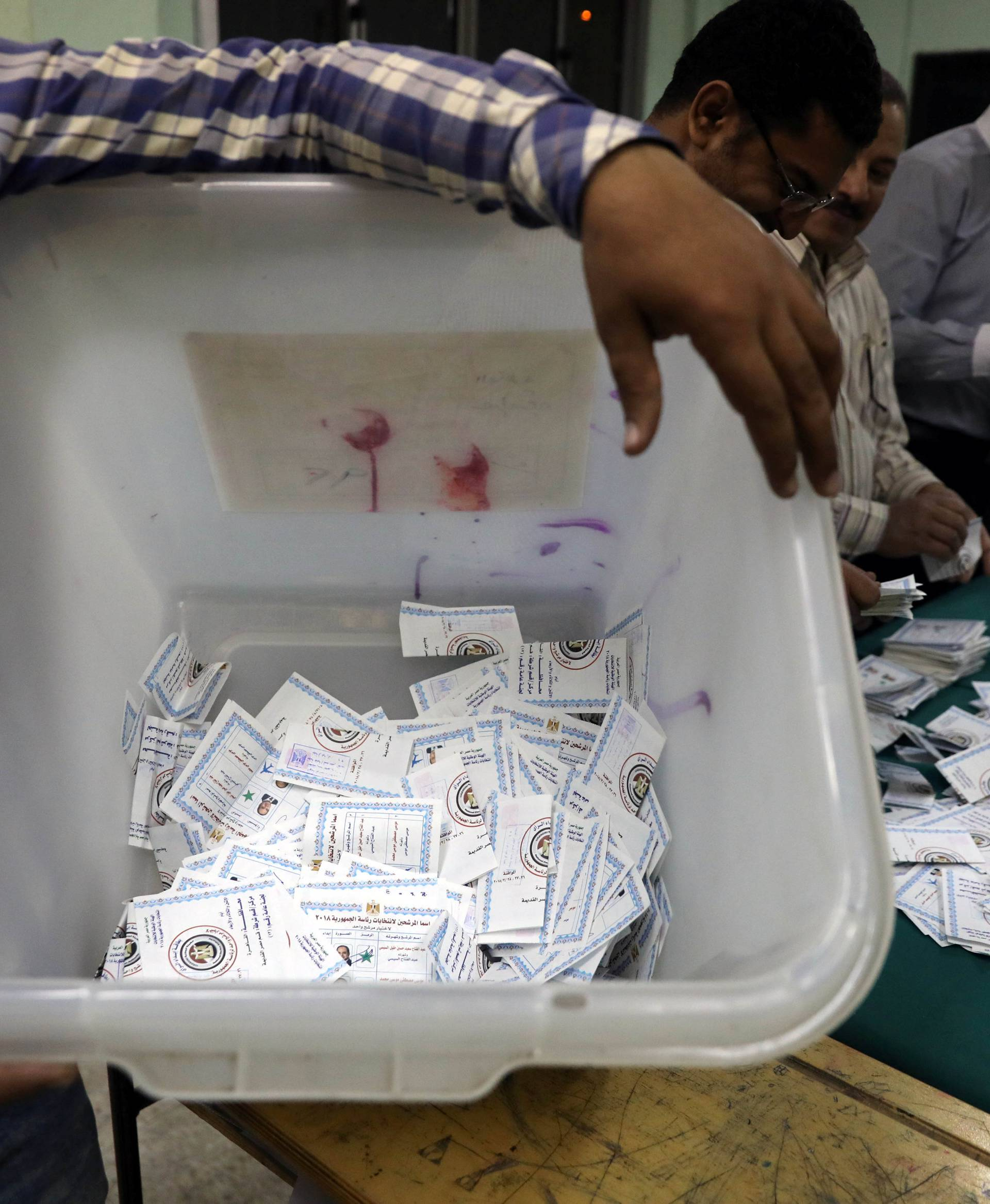 Man carries a ballot box as electoral workers sort ballots to count votes during the presidential election in Cairo