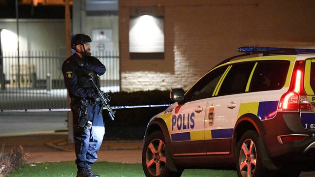 A police officer guards outside a cordoned area surrounding the police station in Helsingborg