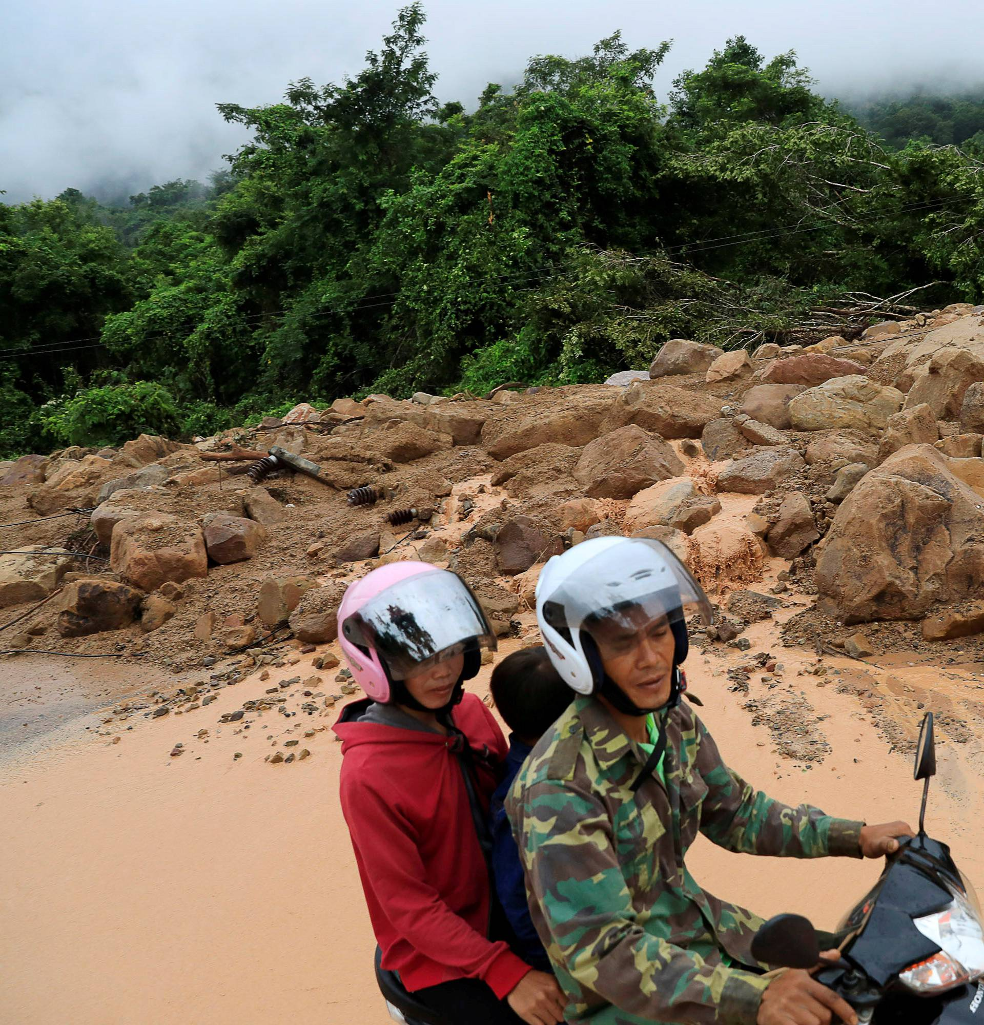 People ride a motorcycle past an area affected by landslide after the Xepian-Xe Nam Noy hydropower dam collapsed in Attapeu province