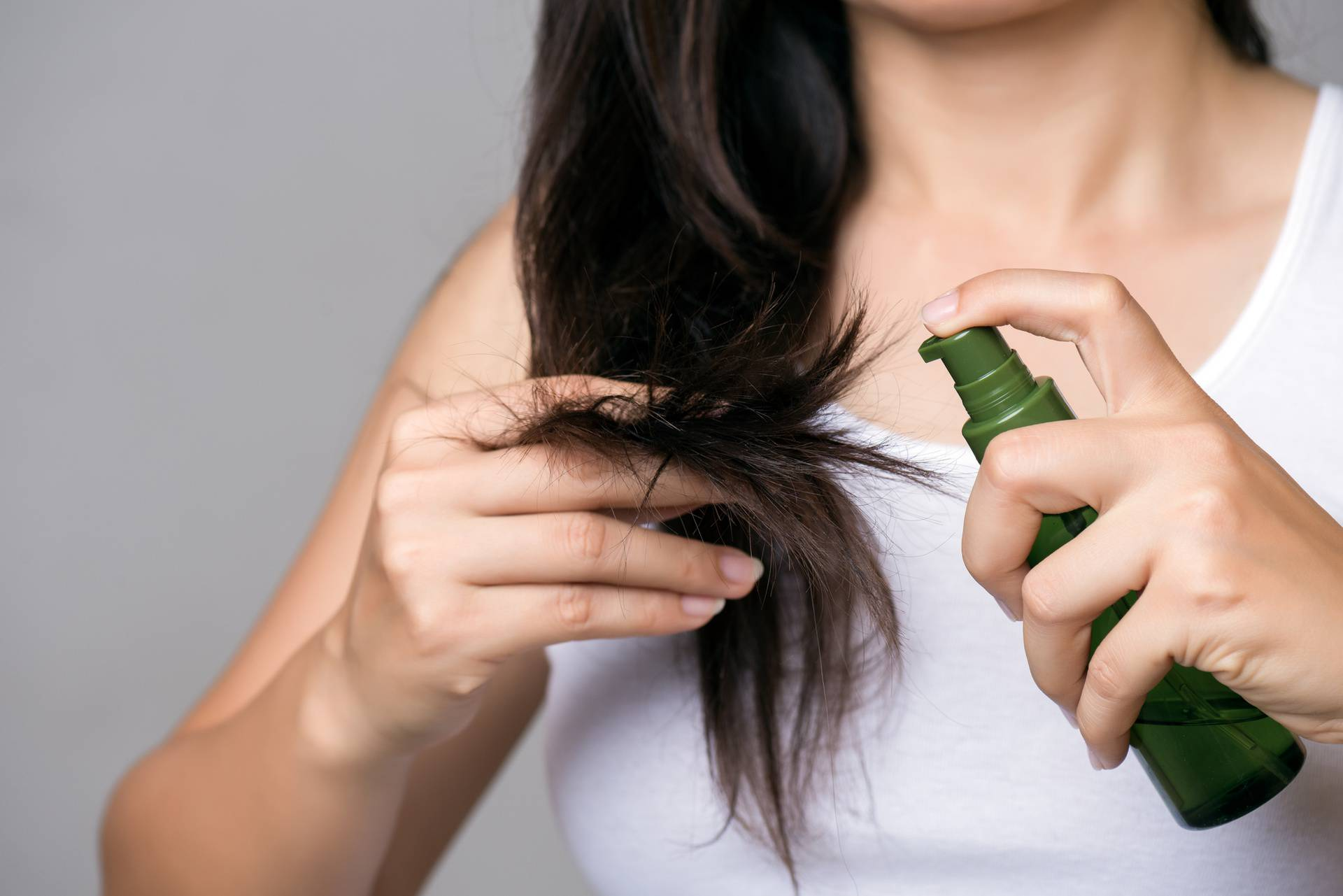 Healthy concept. Woman hand holding damaged long hair with Oil Hair Treatment.