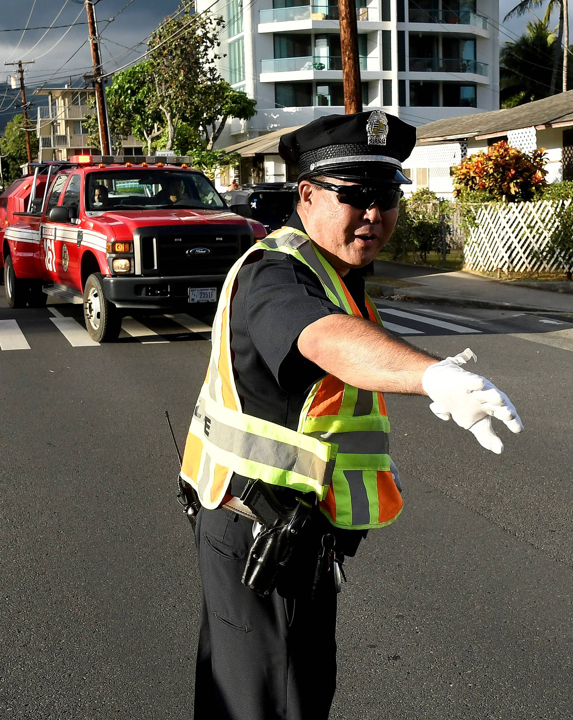 A police officer directs a fire truck to the Marco Polo apartment building after a fire broke out in it in Honolulu, Hawaii.