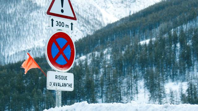 Road signs are pictured on a snow-covered road in Saint-Pancrace as winter weather bringing snow and freezing temperatures continues in France