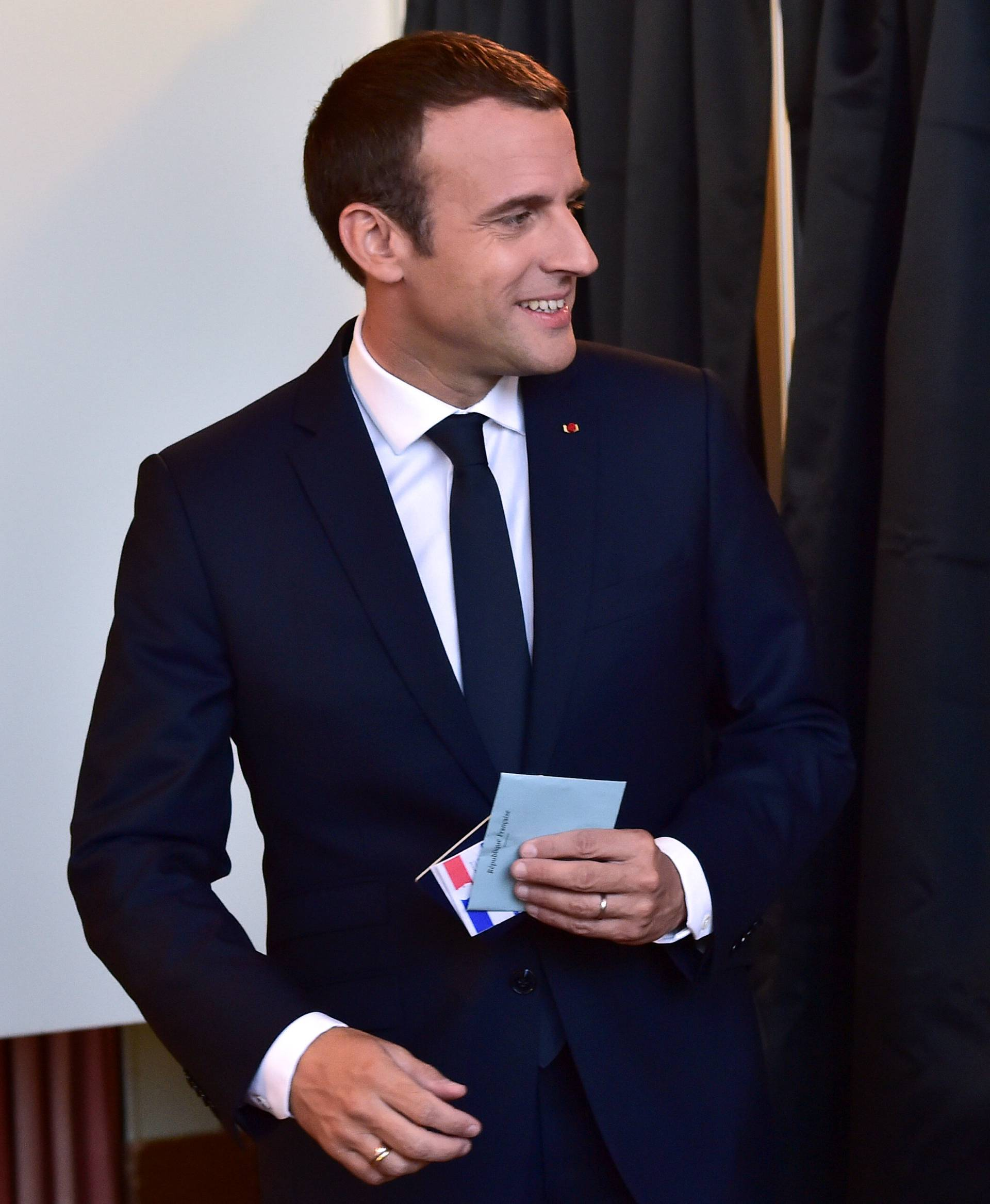 French President Emmanuel Macron hold his ballot before voting at a polling station in the second round parliamentary elections in Le Touquet