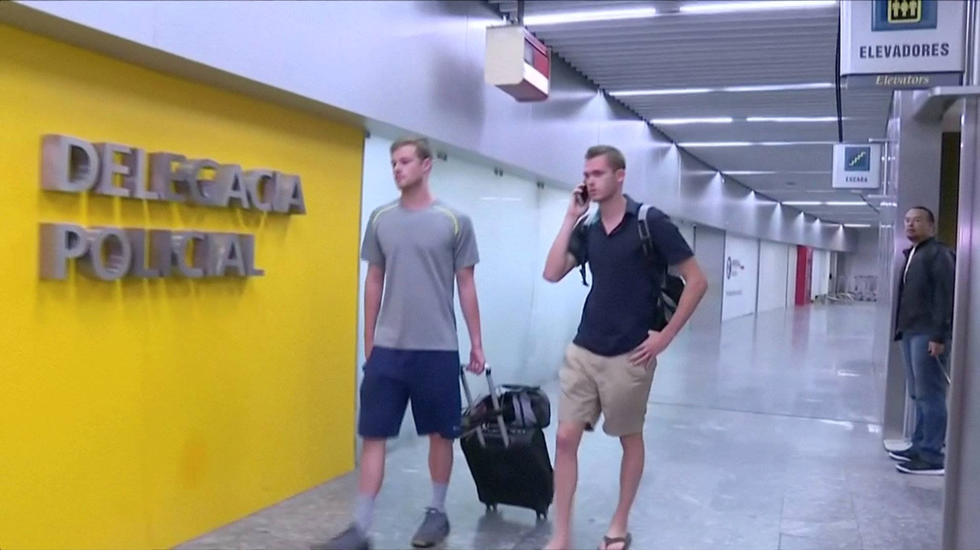U.S. Olympic swimmers Gunnar Bentz and Jack Conger walk to the airport police station office at Rio's international airport in this still frame taken from video