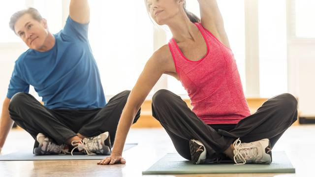 Fit couple practicing yoga on mat at home