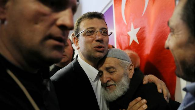 FILE PHOTO: Ekrem Imamoglu, main opposition CHP candidate for mayor of Istanbul, embraces his supporter at his election campaign office in Istanbul