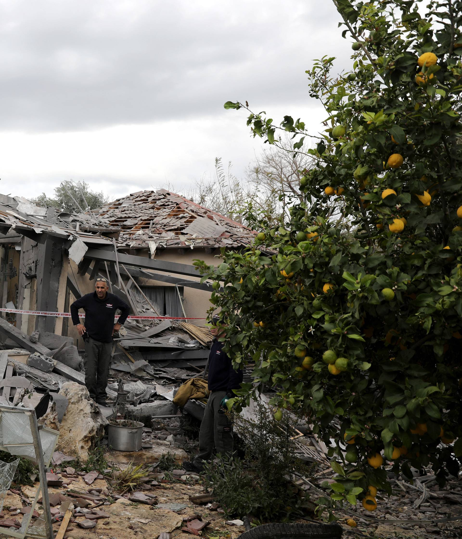 A police sapper inspects a damaged house that was hit by a rocket north of Tel Aviv Israel
