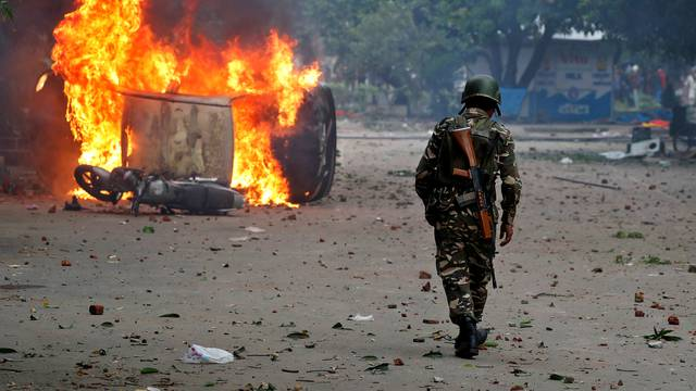 A member of the security forces walks towards a burning vehicles  during violence in Panchkula