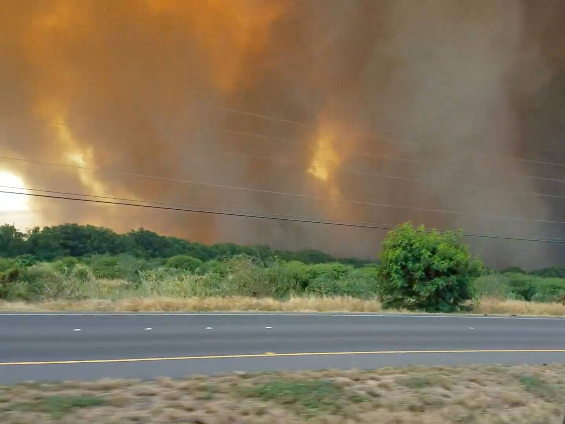 A thick plume of smoke hovers over a wildfire next to a road in Maui