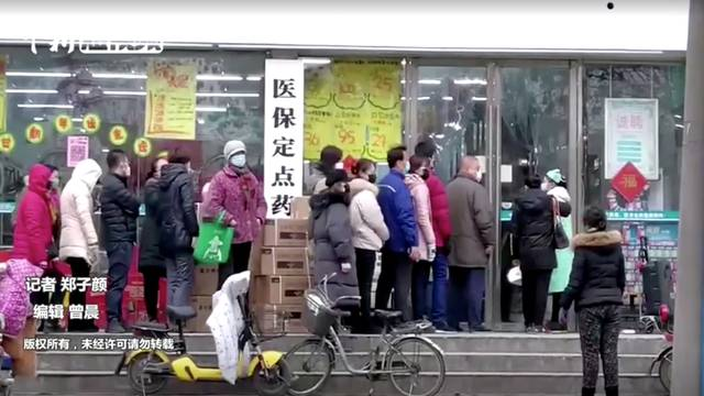 FILE PHOTO: People wearing masks queue at a shop in Wuhan