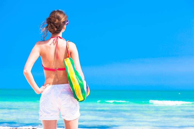 Woman in bikini and sunglasses with beach bag