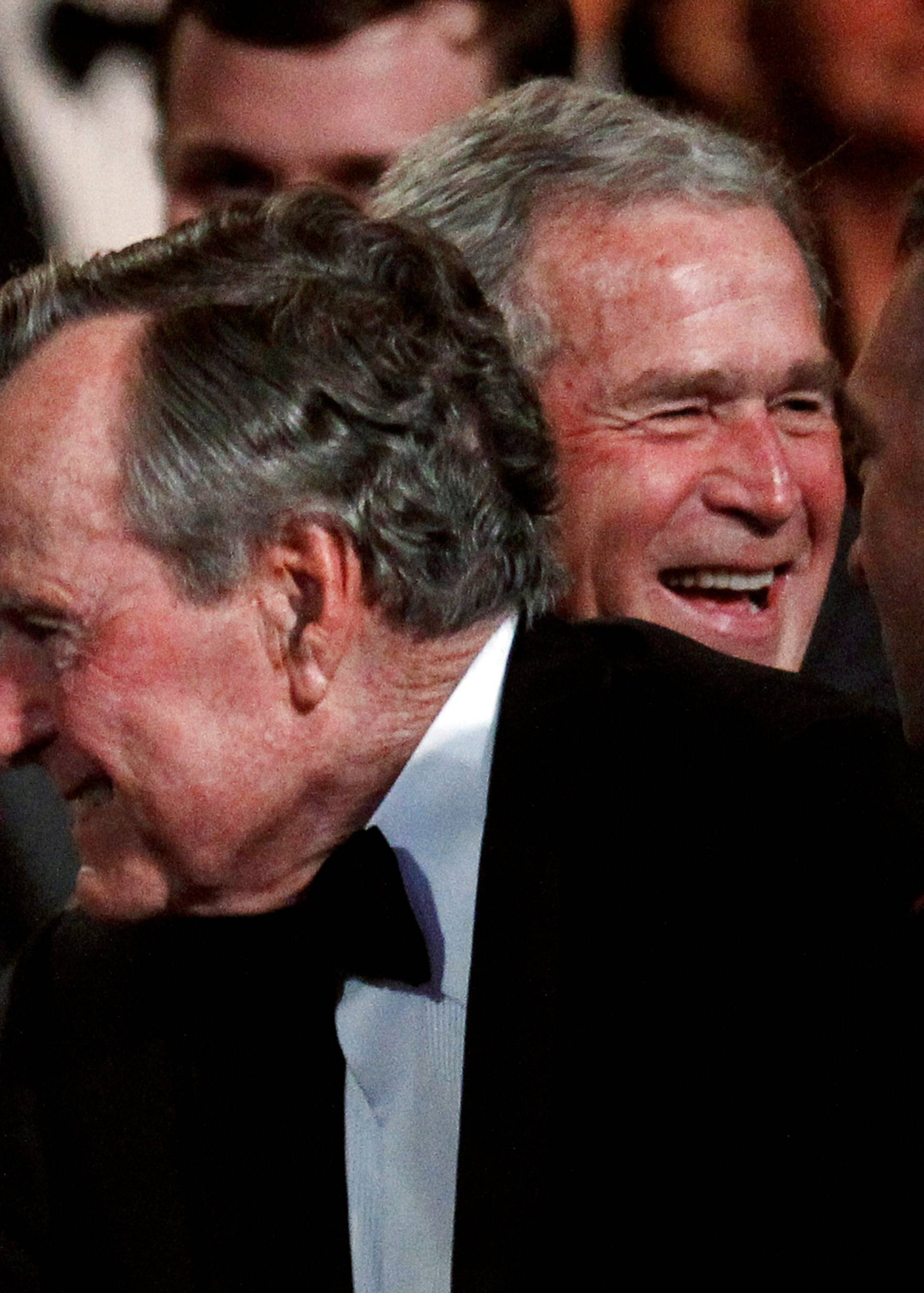 FILE PHOTO: Former U.S. President George. H.W. Bush (C) smiles at his wife Barbara (L), as their son former President George W. Bush (R) laughs in Washington