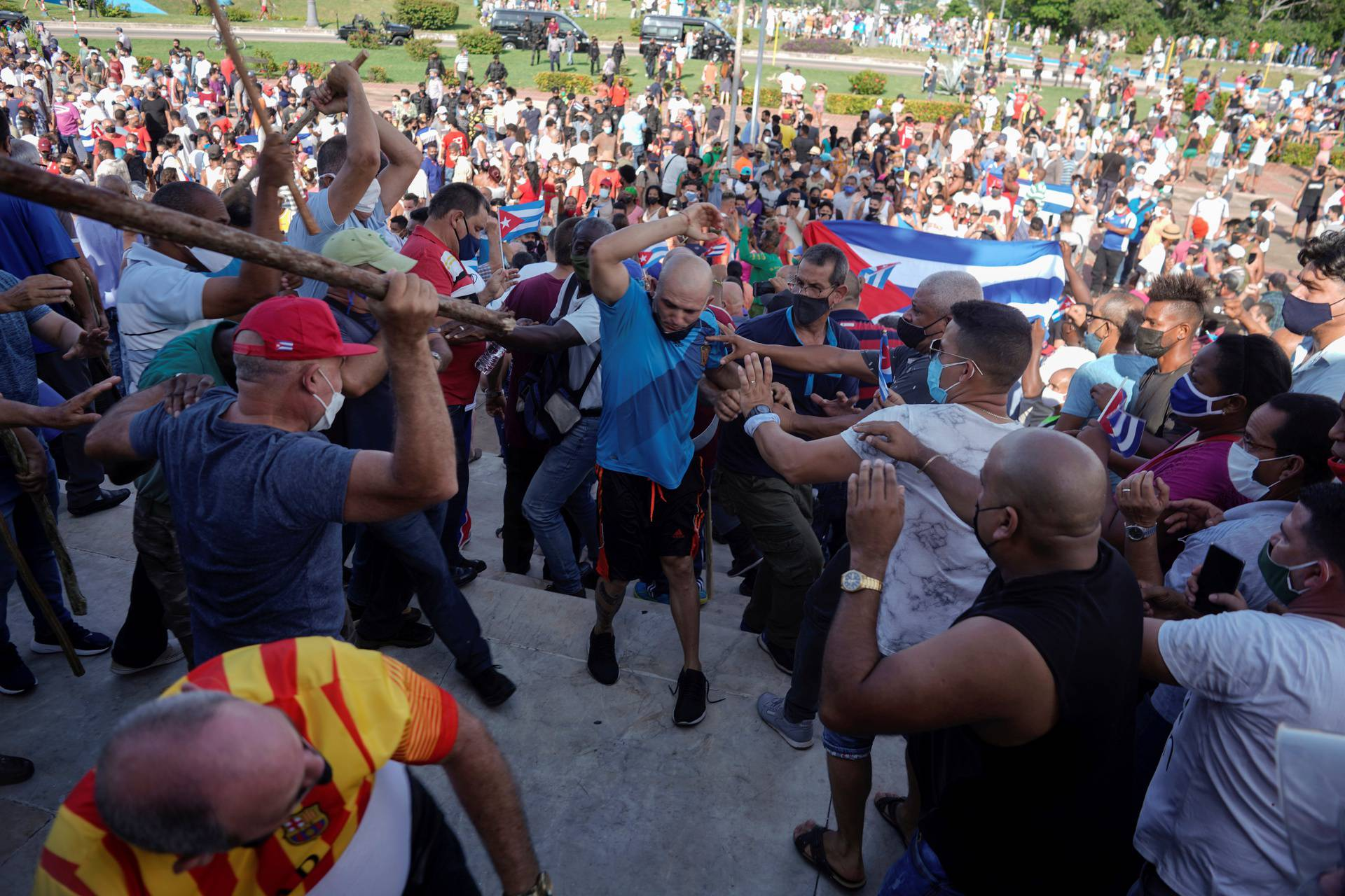People clash with plain clothes police during protests against and in support of the government, in Havana