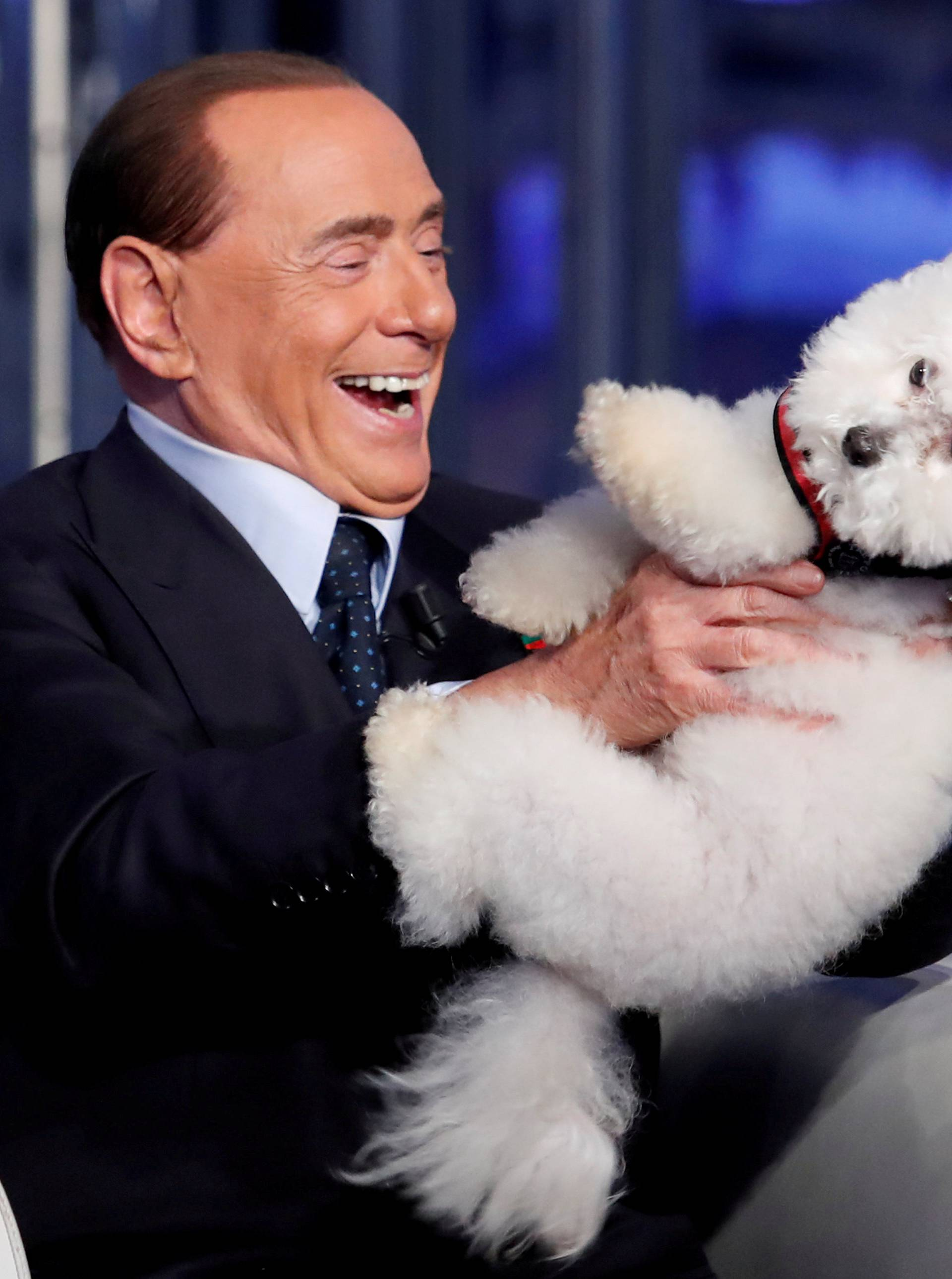 """FILE PHOTO: Italy's former PM Berlusconi plays with a dog during the television talk show """"Porta a Porta"""" in Rome"""