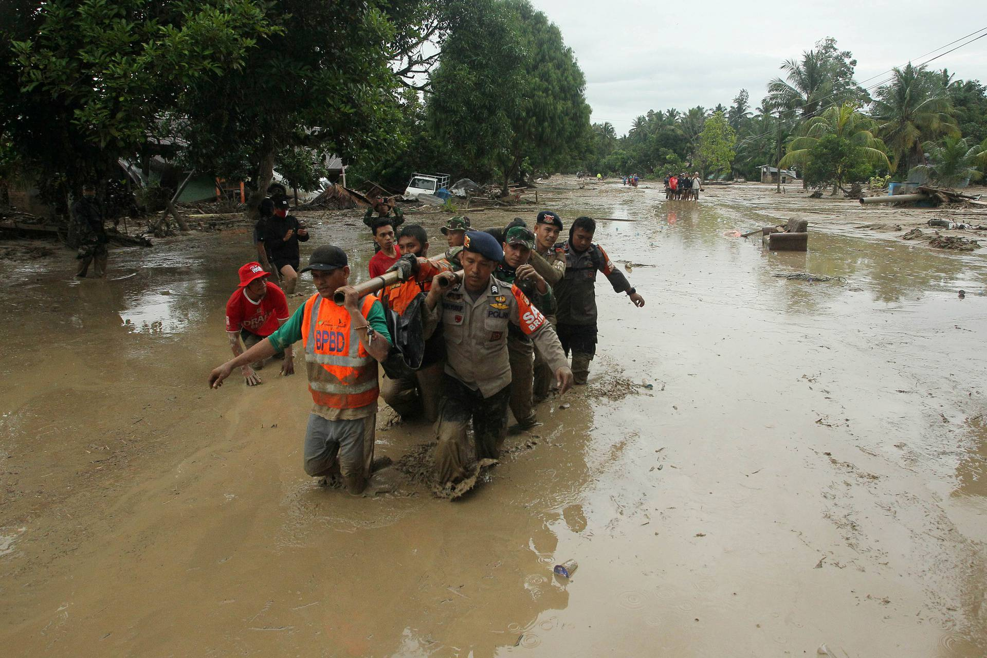 Officers evacuate victims in Radda Village, following flash floods that left several dead and dozens remain missing, in North Luwu in Sulawesi