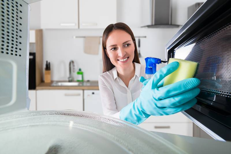 Woman Cleaning Microwave With Spray Bottle And Sponge