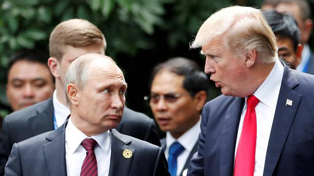 FILE PHOTO: U.S. President Donald Trump and Russia's President Vladimir Putin talk during the family photo session at the APEC Summit in Danang, Vietnam
