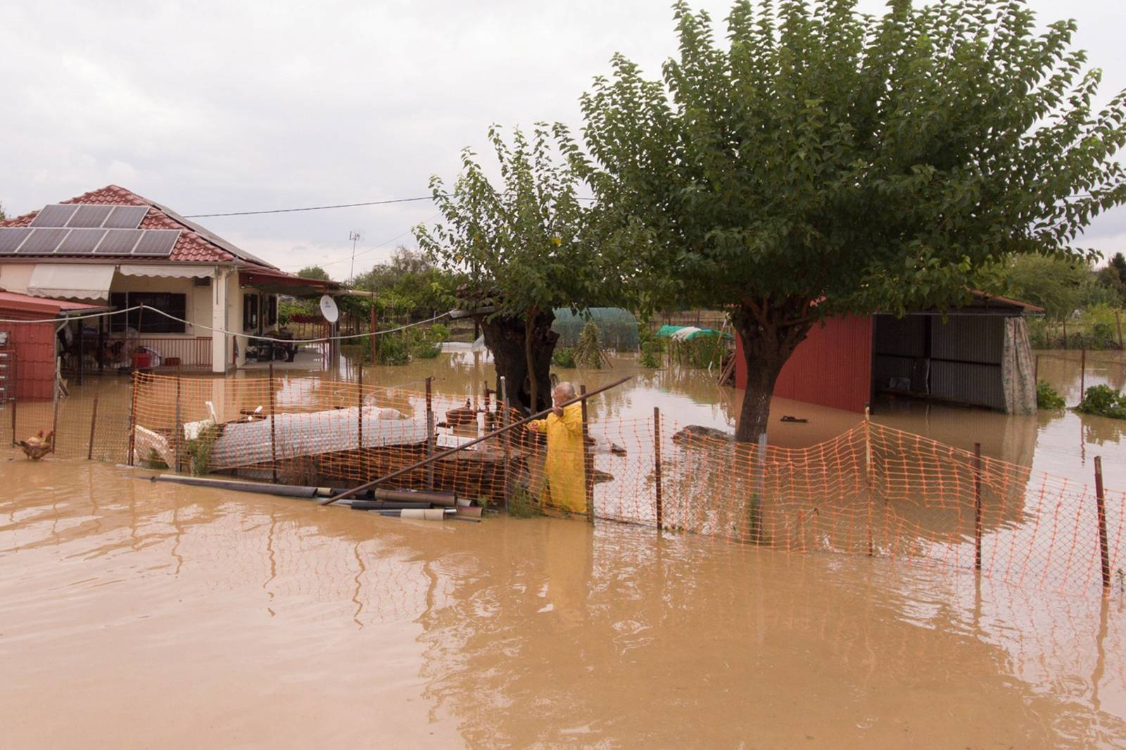 A local is seen in the yard of his flooded house following a storm near the village of Artesiano