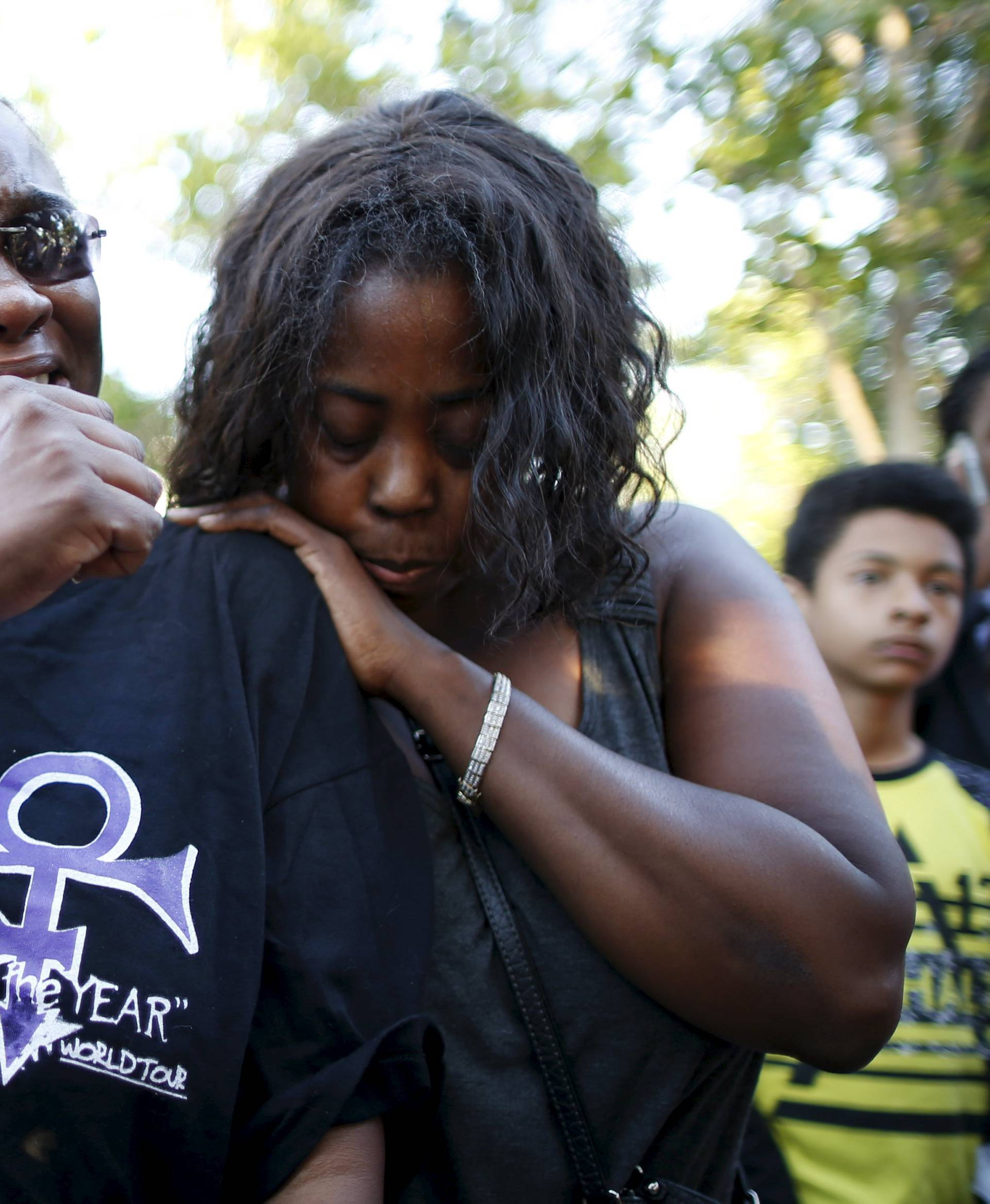 Loretta Thomas, 45, and Deshone, 50, listen to a Prince song at a vigil to celebrate the life and music of deceased musician Prince in Los Angeles