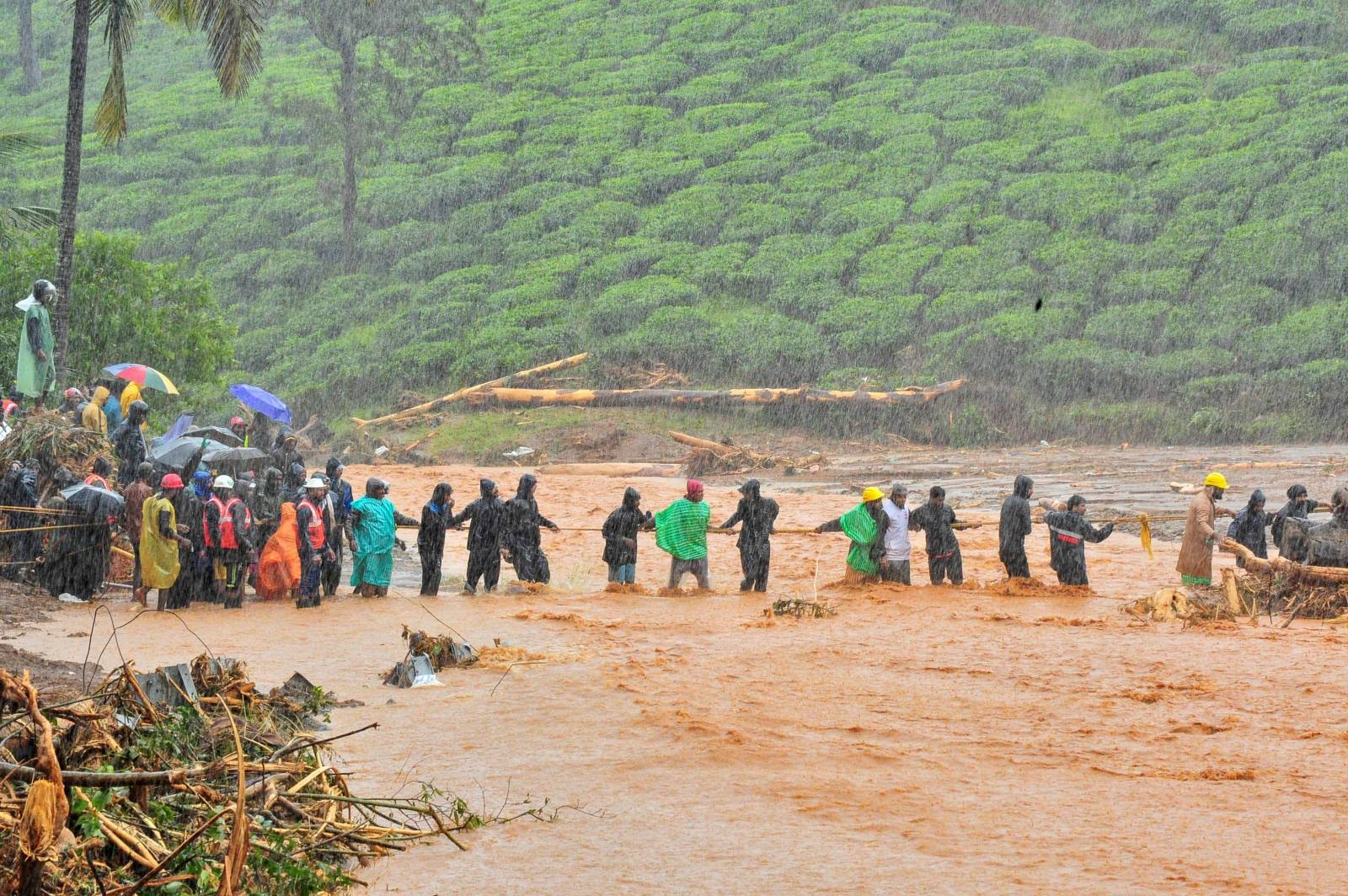 Rescuers help people to cross a flooded area after a landslide caused by torrential monsoon rains in Meppadi in Wayanad