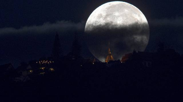 The supermoon is partly covered by clouds as it sets behind Wat Phrathat Doi Suthep in the northern capital of Chiang Mai