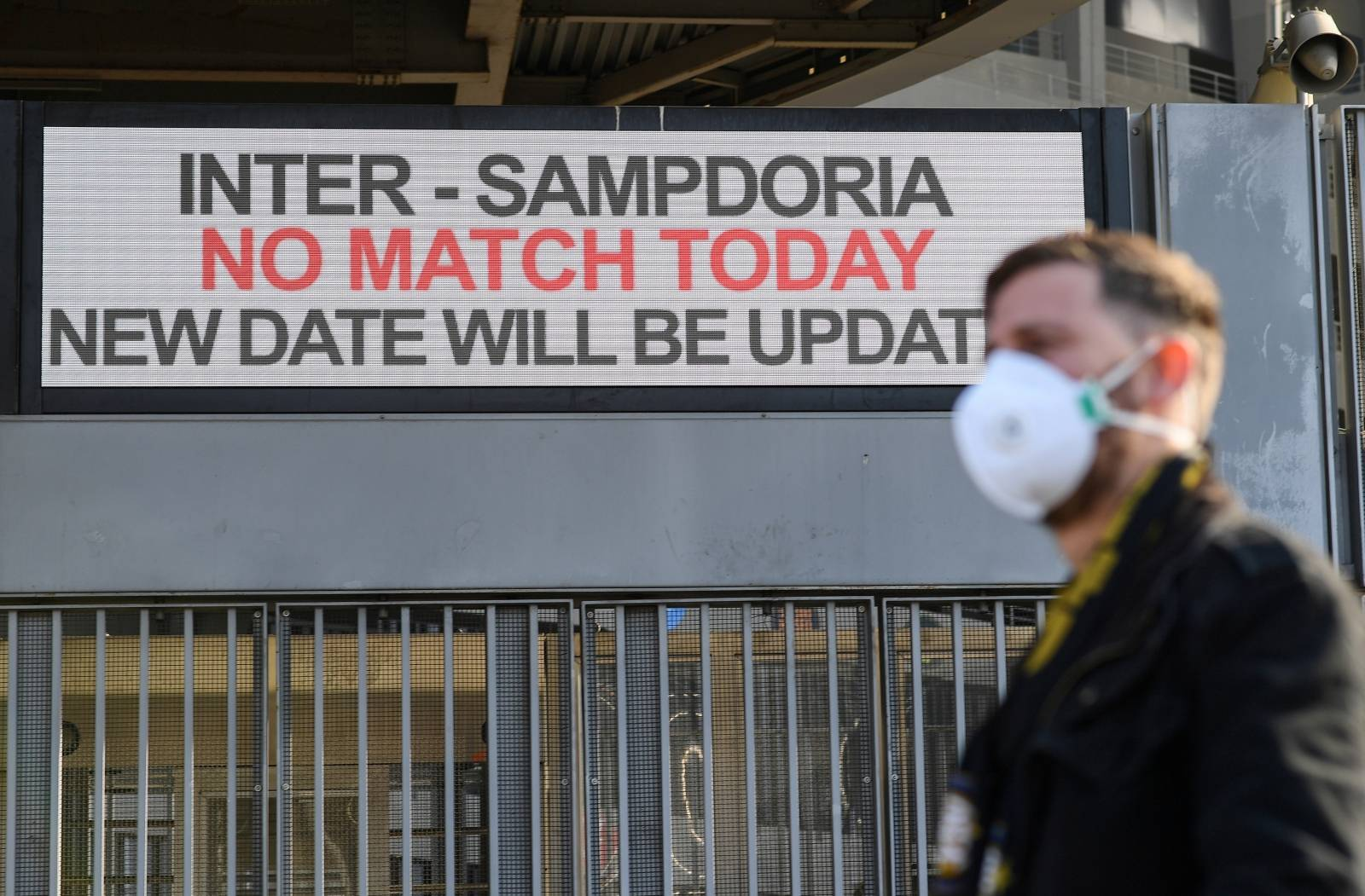 A man wearing a face mask stands outside the San Siro stadium after the Inter Milan v Sampdoria Serie A match was cancelled due to an outbreak of the coronavirus in Lombardy and Veneto, in Milan