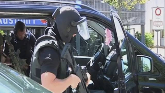 German special police leave their cars after a masked man with a gun and ammunition belt opened fire in a cinema complex in Viernheim